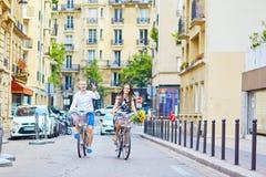 Молодые пары используя велосипеды в Париже, Франции Стоковое фото RF
