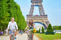 Молодые пары используя велосипеды в Париже, Франции Стоковые Фотографии RF
