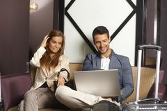 Молодые пары используя компьтер-книжку на лобби гостиницы Стоковое Изображение