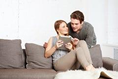 Молодые пары используя компьютер таблетки Стоковые Изображения