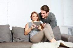Молодые пары используя компьютер таблетки Стоковые Фотографии RF