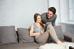 Молодые пары используя компьютер таблетки Стоковые Фото