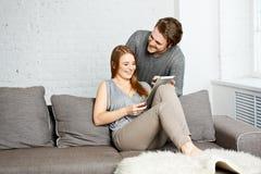 Молодые пары используя компьютер таблетки Стоковые Изображения RF