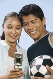 Молодые пары используя мобильный телефон с футбольным мячом Стоковая Фотография