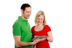 Молодые пары используя ПК таблетки Стоковые Изображения