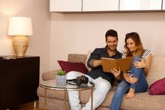 Молодые пары используя таблетку дома Стоковая Фотография RF