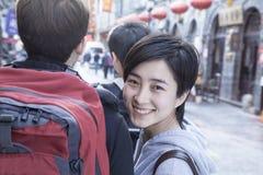 Молодые пары идя вниз с улицы, женщины рассматривая плечо. Стоковая Фотография