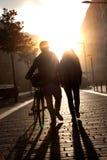 Молодые пары идя вниз с улицы с велосипедом на заходе солнца. Стоковые Фотографии RF