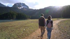 Молодые пары идя вдоль озера видеоматериал