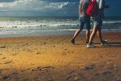 Молодые пары идя вдоль пляжа идя совместно вид сзади концепции Стоковая Фотография RF