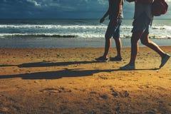 Молодые пары идя вдоль пляжа идя совместно вид сзади концепции Стоковая Фотография