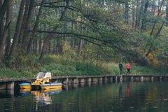 Молодые пары идя около озера в осени Желтый и голубой катамаран в озере против леса осени Стоковое Изображение
