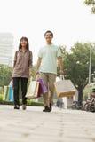 Молодые пары идя с хозяйственными сумками в руках, Пекин, Китай Стоковые Изображения RF