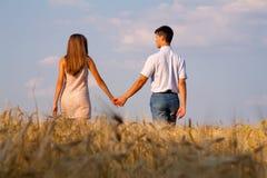 Молодые пары идя через пшеничное поле Стоковые Фотографии RF
