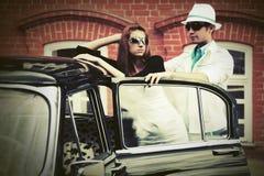 Молодые пары моды рядом с винтажным автомобилем Стоковые Изображения