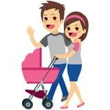 Молодые пары нажимая прогулочную коляску Стоковая Фотография