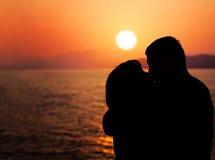 Молодые пары наслаждаясь заходом солнца на пляже Стоковое Изображение