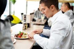 Молодые пары наслаждаясь обедом на ресторане Стоковая Фотография RF