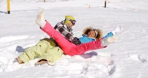 Молодые пары наслаждаясь frolic в снеге стоковая фотография rf