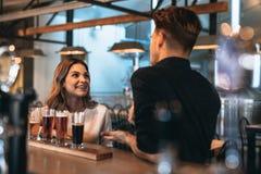 Молодые пары на баре с различными пив ремесла Стоковые Фотографии RF