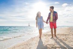 Молодые пары на летних каникулах пляжа, счастливом усмехаясь человеке и взморье женщины идя Стоковое Изображение RF