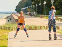 Молодые пары на коньках ролика ехать outdoors Стоковое фото RF
