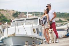Молодые пары на прогулке в гавани с собакой Стоковое Фото