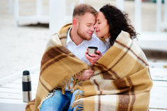 Молодые пары обнимая и покрытые при теплое одеяло сидя o Стоковое Фото