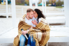 Молодые пары обнимая и покрытые при теплое одеяло сидя o Стоковая Фотография