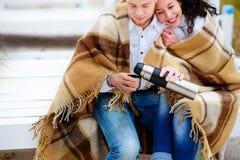 Молодые пары обнимая и покрытые при теплое одеяло сидя o Стоковое фото RF