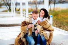 Молодые пары обнимая и покрытые при теплое одеяло сидя o Стоковое Изображение RF