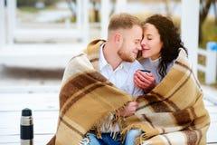 Молодые пары обнимая и покрытые при теплое одеяло сидя o Стоковые Фотографии RF