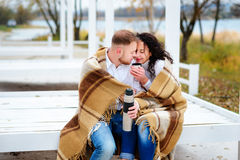 Молодые пары обнимая и покрытые при теплое одеяло сидя o Стоковые Изображения
