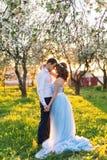 Молодые пары обнимая на заходе солнца в зацветая весне садовничают Влюбленность и романтичная тема Стоковое фото RF