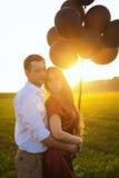 Молодые пары обнимая на заходе солнца Стоковые Фото