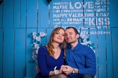 Молодые пары обнимая сидеть в интерьере Стоковые Изображения