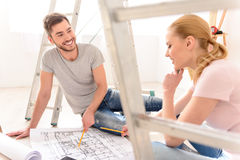 Молодые пары обсуждая план квартир стоковая фотография