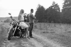 Молодые пары около велосипеда в поле Стоковое Фото