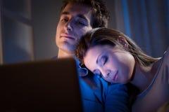 Молодые пары дома с компьтер-книжкой Стоковые Изображения RF