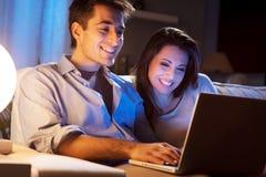 Молодые пары дома с компьтер-книжкой Стоковые Фотографии RF