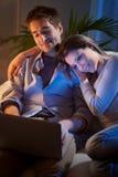 Молодые пары дома с компьтер-книжкой Стоковая Фотография