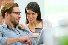 Молодые пары дома ходя по магазинам на интернете с таблеткой стоковое изображение