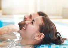 Молодые пары ослабляя в воде в курорте спы Стоковая Фотография RF
