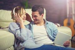 Молодые пары ослабляя на кресле с компьтер-книжкой в их живущей комнате Стоковое Фото
