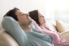 Молодые пары ослабляя на софе, глаза закрыли, взгляд со стороны Стоковая Фотография RF