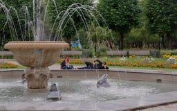 Молодые пары ослабляя около фонтана Стоковое Изображение