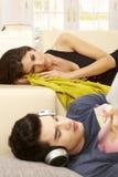 Молодые пары отдыхая дома Стоковое Фото