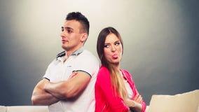 Молодые пары после ссоры сидя на софе спина к спине Стоковые Фотографии RF