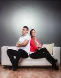 Молодые пары после ссоры сидя на софе спина к спине Стоковые Фото