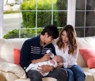 Молодые пары подавая их грудной ребенок на белой софе стоковое фото